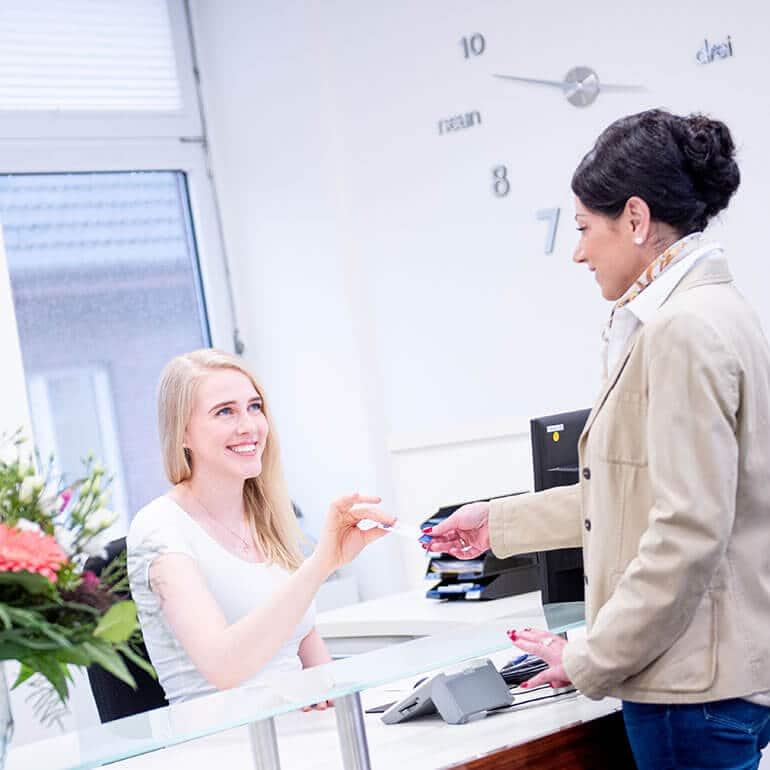 KFO Stelz | Frau Heyen nimmt Terminkarte der Patientin entgegen